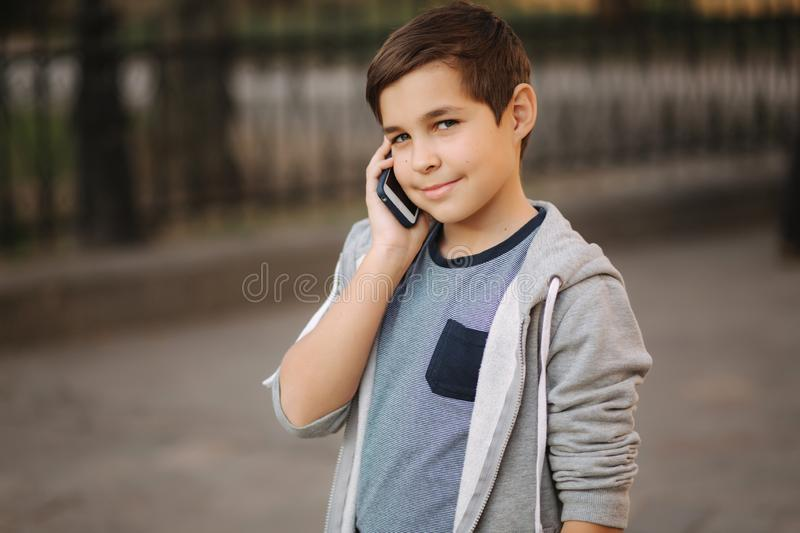 Young boy call his mom. Teenage boy use phone outside royalty free stock photos
