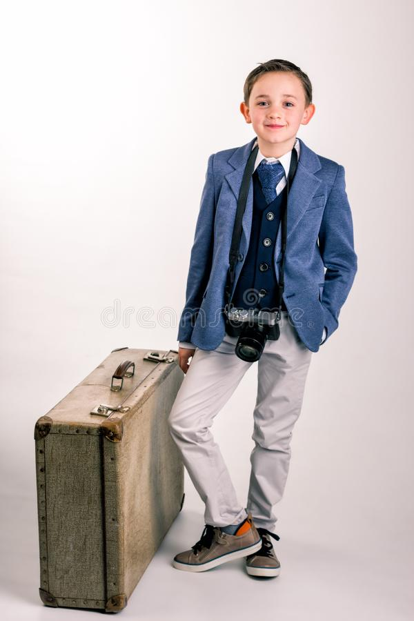 Young boy with camera and suitcase stock image