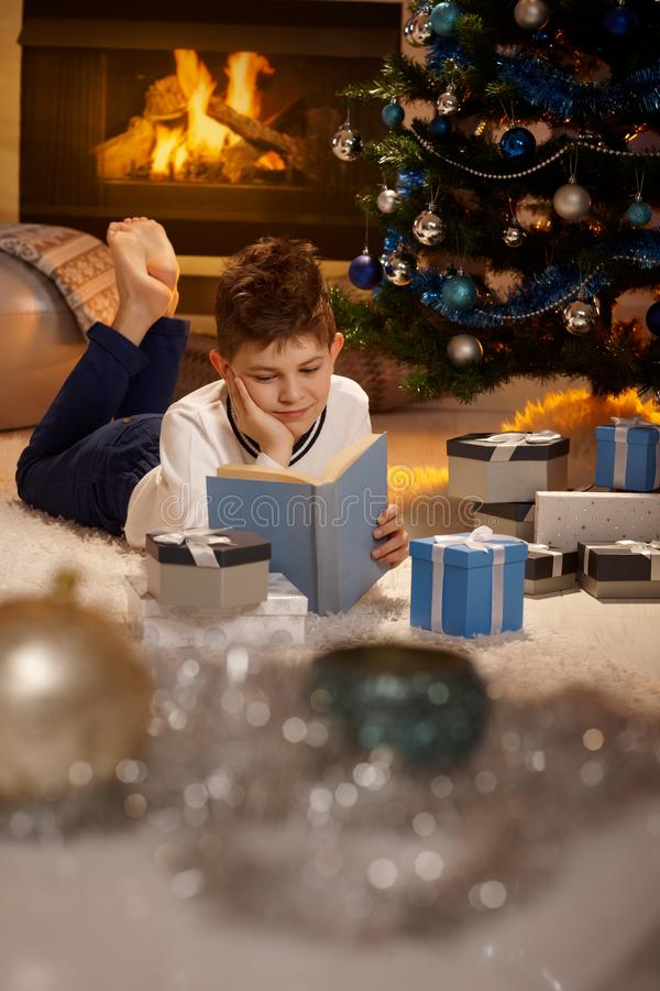 Young boy at christmas time. Young boy lying on front by christmas tree, reading book surrounded by christmas presents stock photography