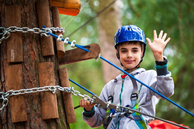 Young boy climbing pass obstacles in rope. Child in forest adventure park royalty free stock images