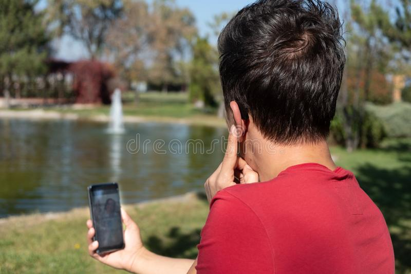 Young boy communicating with sign language at smart phone stock photo