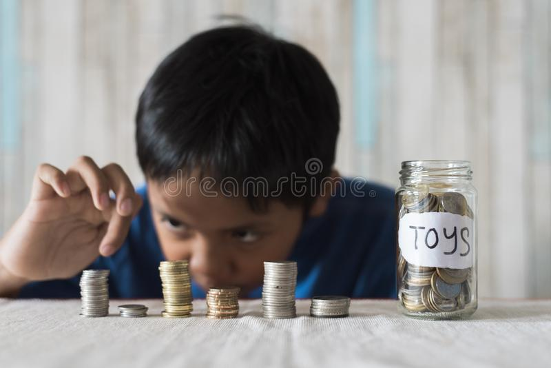Young boy counting his coins/savings to buy dream toys. stock image