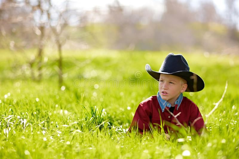 Young boy in cowboy hat. Relaxing in green countryside field or meadow royalty free stock photos