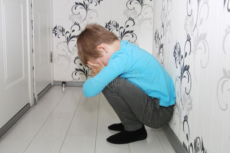A young boy is crying in the hallway. Lonely boy royalty free stock photo