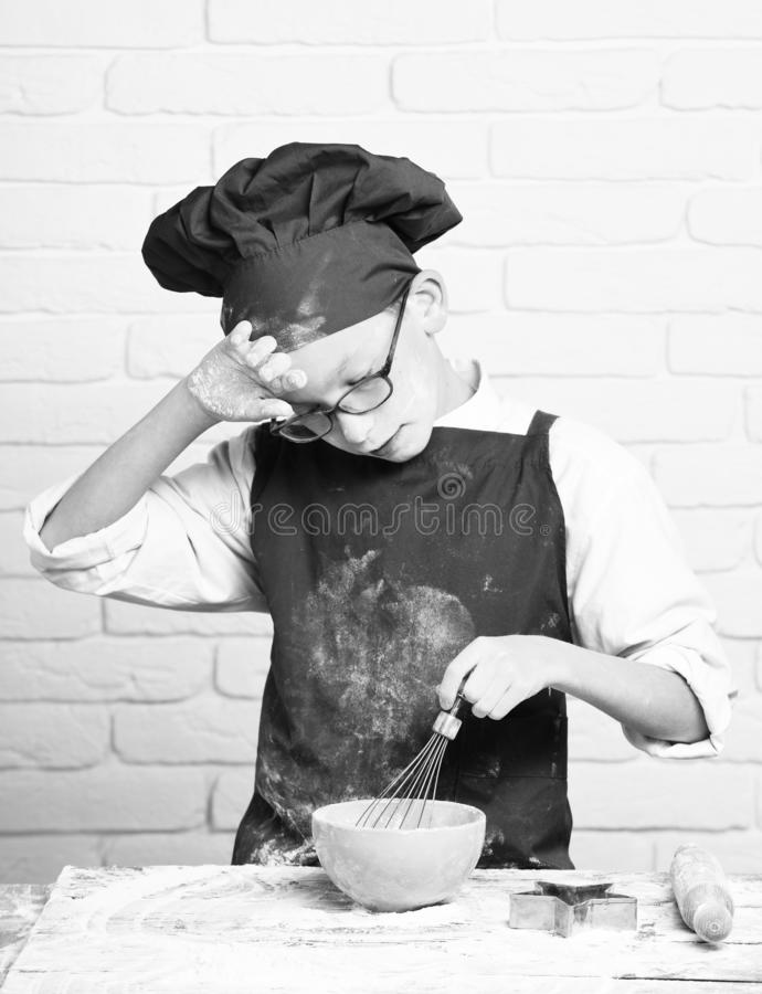 Young boy cute cook chef in red uniform and hat on stained face flour with glasses standing near table with rolling pin. And cooking with kitchen whisk in stock photography