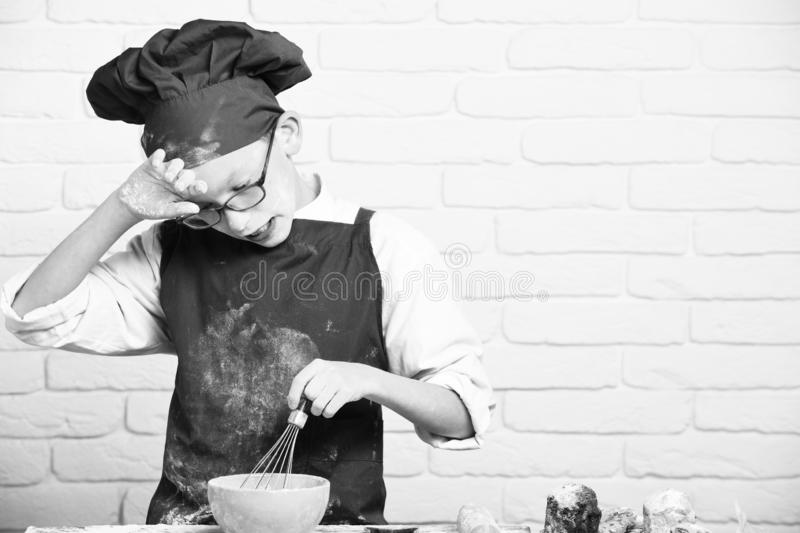 Young boy cute cook chef in red uniform and hat on stained face flour with glasses standing near table with rolling pin. And cooking with kitchen whisk in stock images