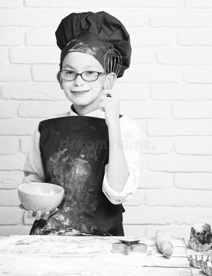 Young boy cute cook chef in red uniform and hat on stained face flour with glasses standing near table with rolling pin. And holding kitchen whisk and turquoise stock photo