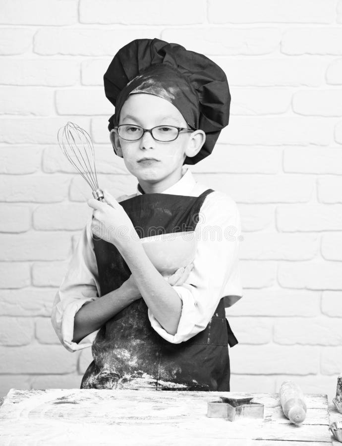 Young boy cute cook chef in red uniform and hat on stained face flour with glasses standing near table with rolling pin. And holding kitchen whisk and turquoise royalty free stock photography