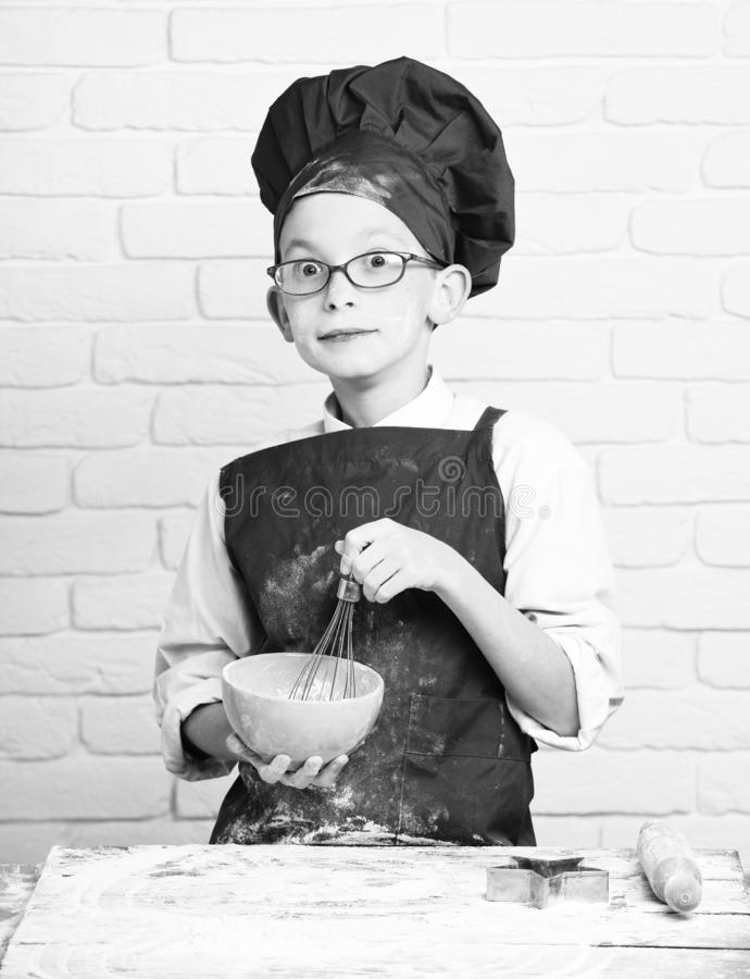 Young boy cute cook chef in red uniform and hat on stained face flour with glasses standing near table with rolling pin. And cooking with kitchen whisk in royalty free stock photos