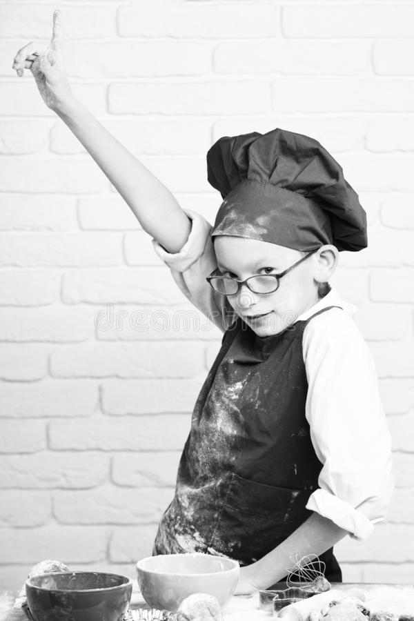 Young boy cute cook chef in red uniform and hat on stained face with glasses standing near table with colorful bowls. Tasty cakes, rolling pin and kitchen royalty free stock photos
