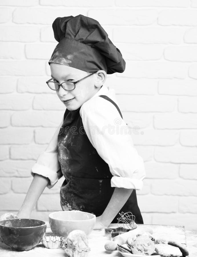 Young boy cute cook chef in red uniform and hat on stained face with glasses standing near table with colorful bowls. Tasty cakes, rolling pin and kitchen royalty free stock photography