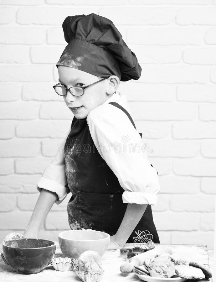 Young boy cute cook chef in red uniform and hat on stained face with glasses standing near table with colorful bowls. Tasty cakes, rolling pin and kitchen stock image