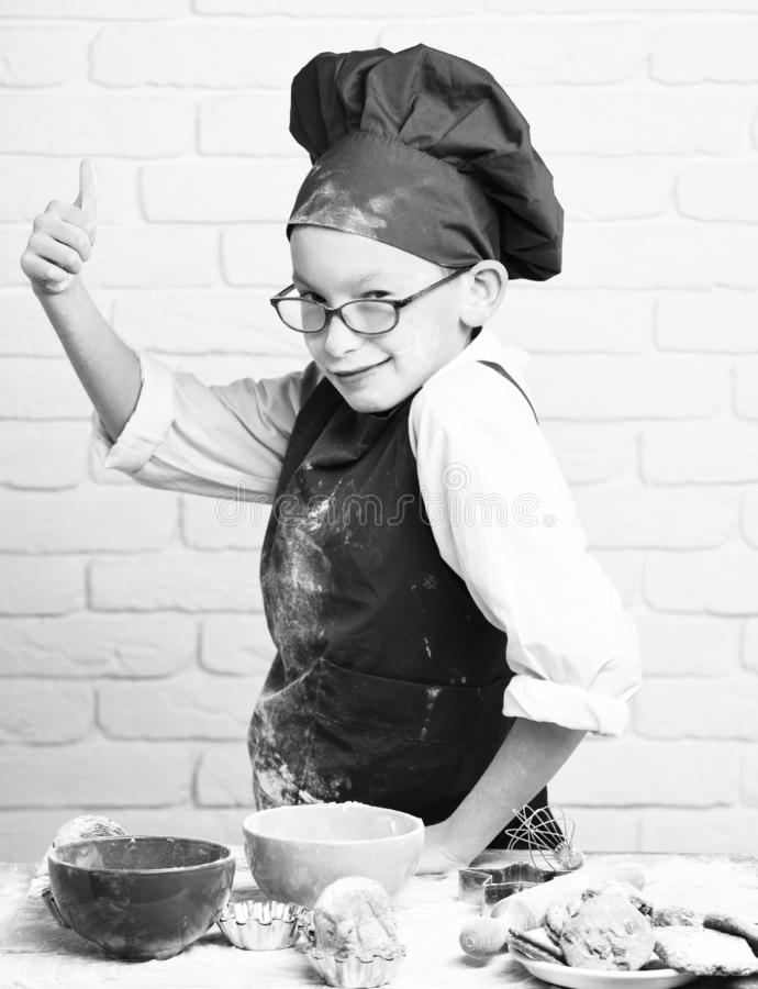 Young boy cute cook chef in red uniform and hat on stained face with glasses standing near table with colorful bowls. Tasty cakes, rolling pin and kitchen stock photography