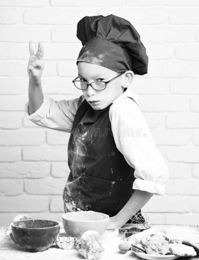 Young boy cute cook chef in red uniform and hat on stained face with glasses standing near table with colorful bowls. Tasty cakes, rolling pin and kitchen stock photos