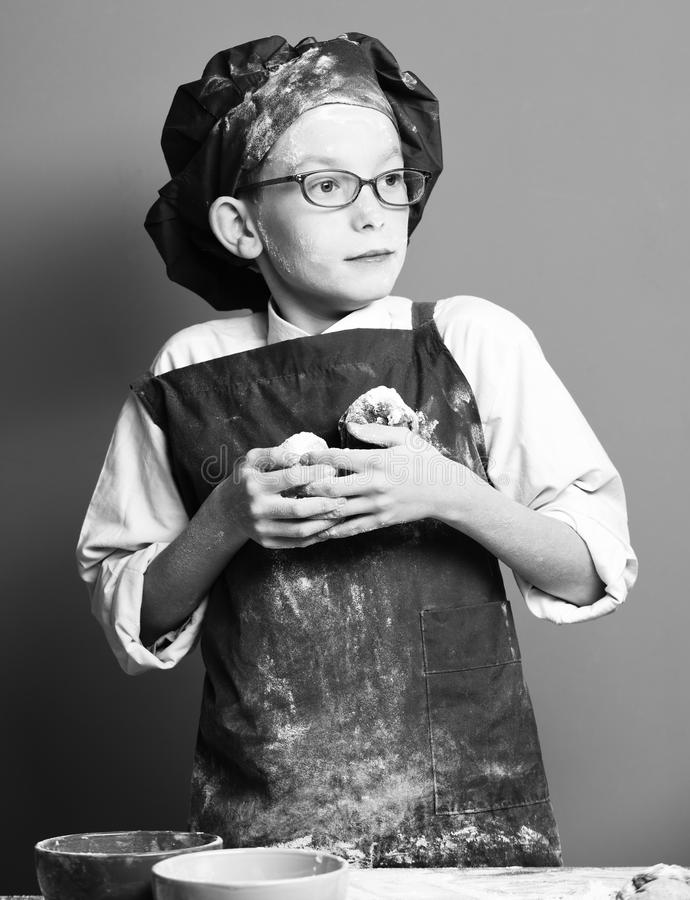 Young boy cute cook chef in uniform and hat on stained face flour with glasses standing near table with colorful bawls. And holding tasty chocolate cakes on red royalty free stock images