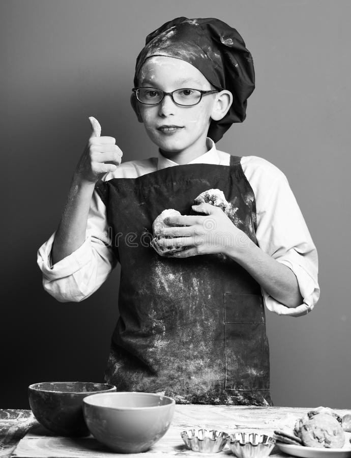 Young boy cute cook chef in uniform and hat on stained face flour with glasses standing near table with colorful bawls. And holding tasty chocolate cakes on red royalty free stock photography
