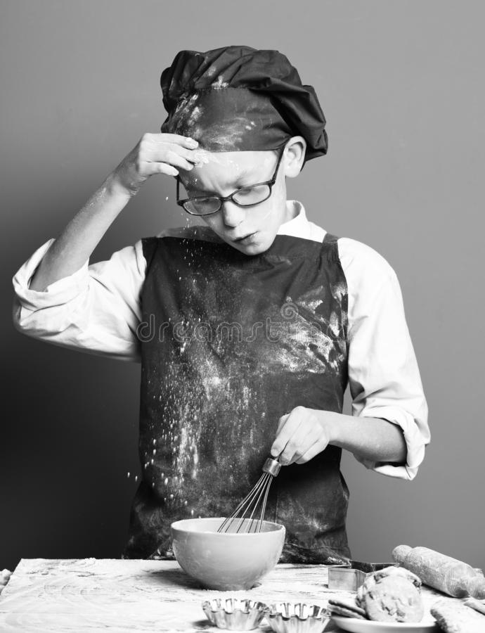 Young boy cute cook chef in uniform and hat on stained face flour with glasses standing near table and cooking with. Kitchen whisk in turquoise bowl on red stock photography
