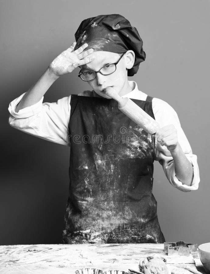 Young boy cute cook chef in uniform and hat on stained face flour with glasses standing near table with rolling pin on. Red studio background stock photos