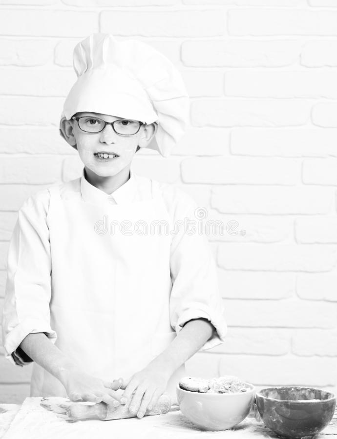 Young boy cute cook chef in white uniform and hat on stained face flour with glasses cooking on table with rolling pin royalty free stock images