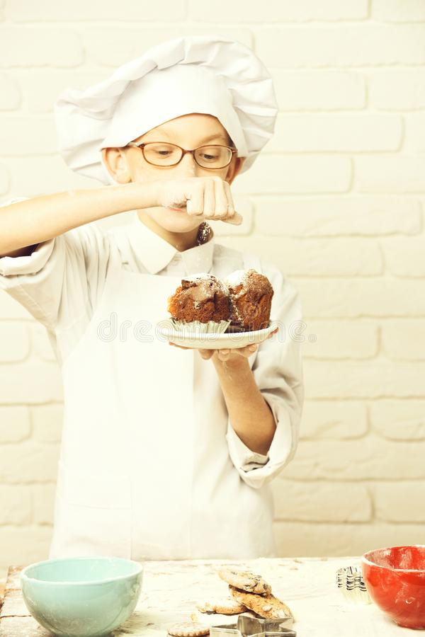 Young boy cute cook chef in white uniform and hat on stained face flour with glasses stand near table with colorful stock images