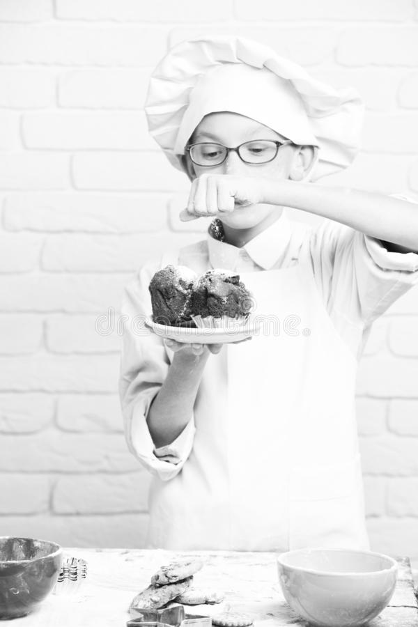 Young boy cute cook chef in white uniform and hat on stained face flour with glasses stand near table with colorful stock photography