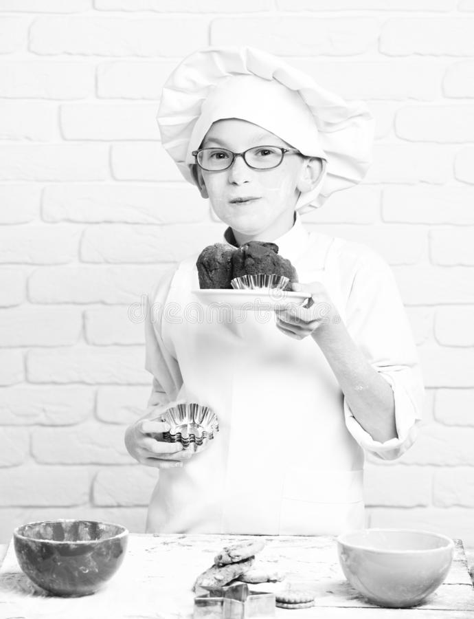 Young boy cute cook chef in white uniform and hat on stained face flour with glasses stand near table with molds for royalty free stock images