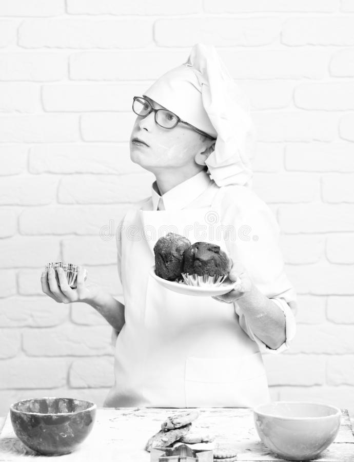 Young boy cute cook chef in white uniform and hat on stained face flour with glasses stand near table with molds for royalty free stock photo
