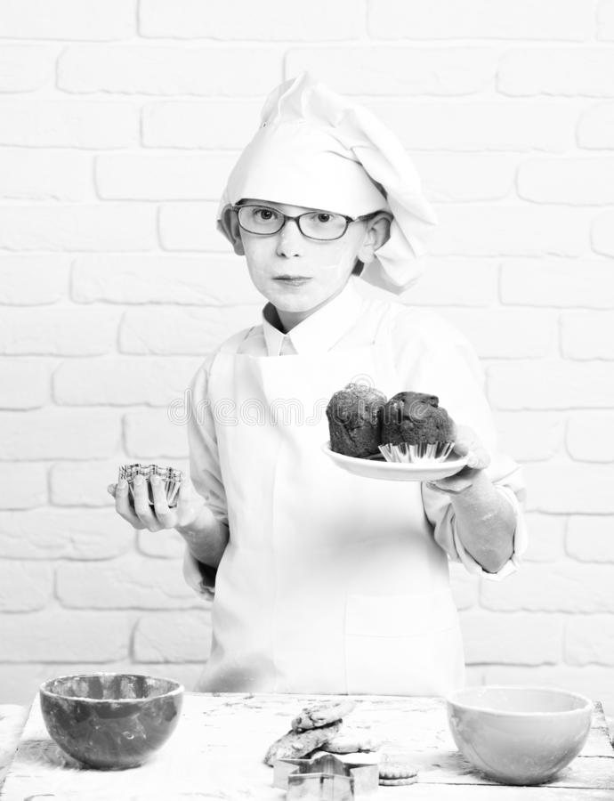 Young boy cute cook chef in white uniform and hat on stained face flour with glasses stand near table with molds for stock photos