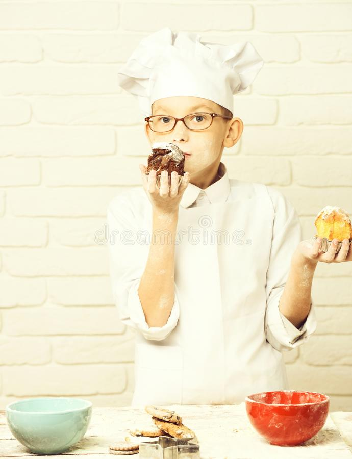 Young boy cute cook chef in white uniform and hat on stained face flour with glasses standing near table with colorful. Bowls and holding chocolate cakes on royalty free stock photo
