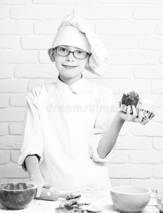 Young boy cute cook chef in white uniform and hat on stained face flour with glasses standing near table with colorful. Bowls and holding chocolate cakes on stock image