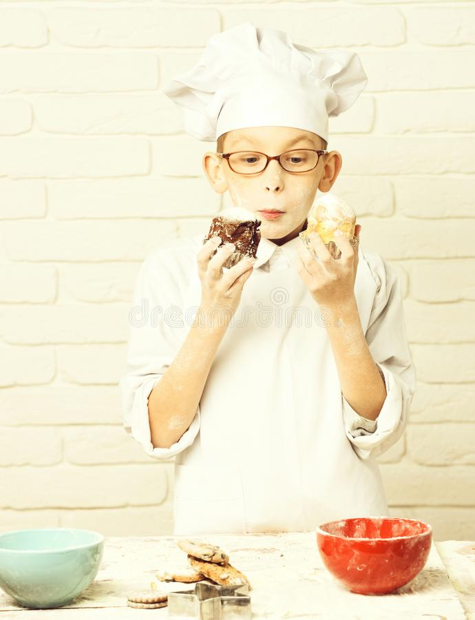 Young boy cute cook chef in white uniform and hat on stained face flour with glasses standing near table with colorful. Bowls and holding chocolate cakes on stock photos