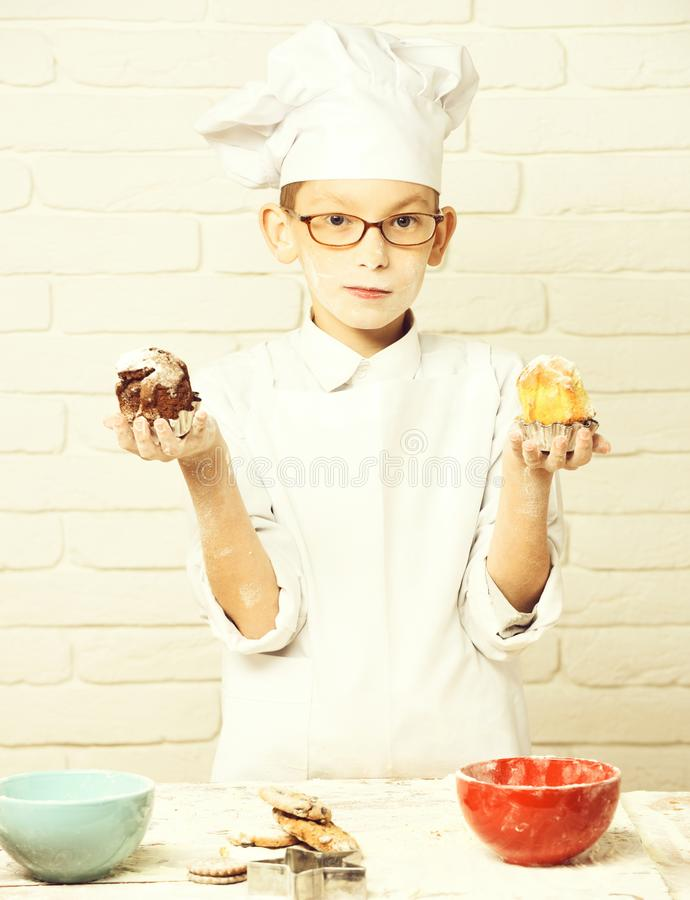 Young boy cute cook chef in white uniform and hat on stained face flour with glasses standing near table with colorful. Bowls and holding chocolate cakes on royalty free stock photos