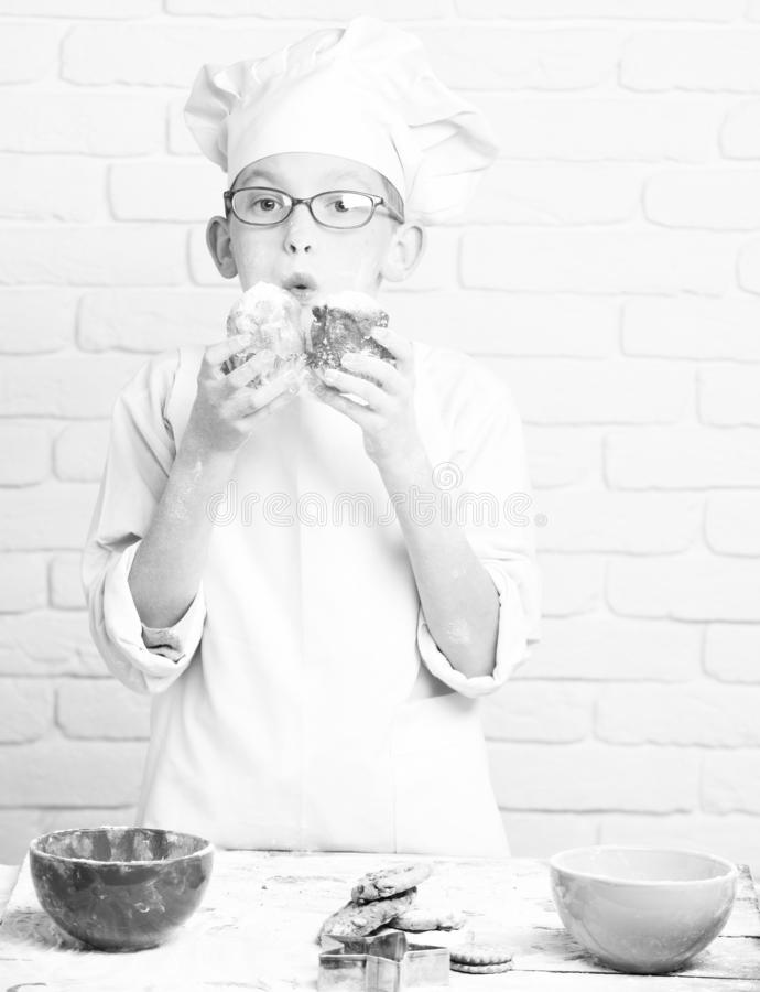 Young boy cute cook chef in white uniform and hat on stained face flour with glasses standing near table with colorful. Bowls and holding chocolate cakes on royalty free stock image