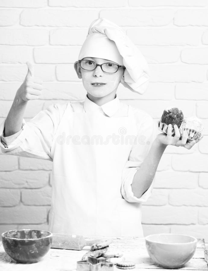 Young boy cute cook chef in white uniform and hat on stained face flour with glasses standing near table with colorful stock images