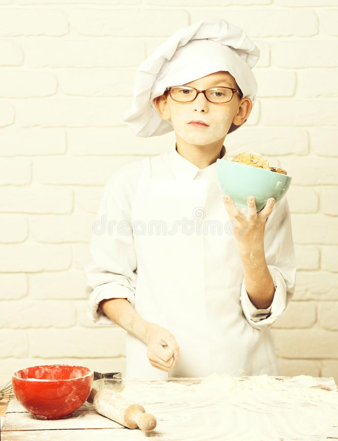 Young boy cute cook chef in white uniform and hat on stained face flour with glasses standing near table with rolling. Pin and holding turquoise bowl with royalty free stock photo