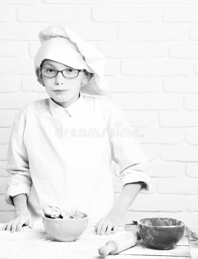 Young boy cute cook chef in white uniform and hat on stained face flour with glasses standing near table with rolling. Pin and colorful bowls with chocolate stock photography
