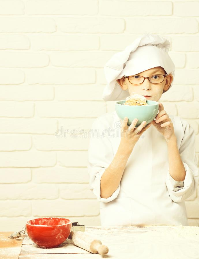Young boy cute cook chef in white uniform and hat on stained face flour with glasses standing near table with rolling. Pin and holding turquoise bowl with royalty free stock images