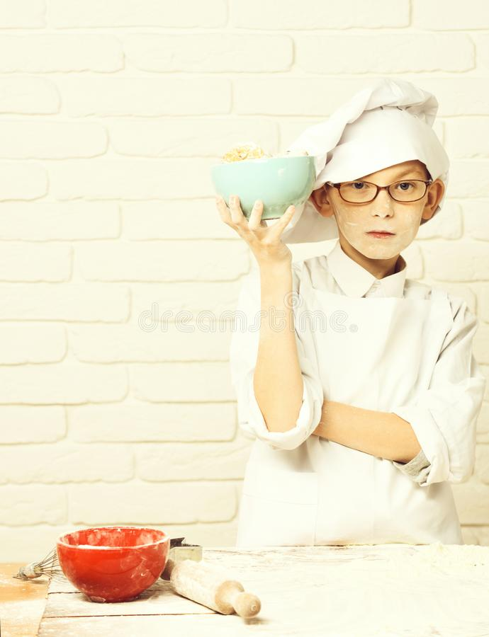Young boy cute cook chef in white uniform and hat on stained face flour with glasses standing near table with rolling. Pin and holding turquoise bowl with stock images