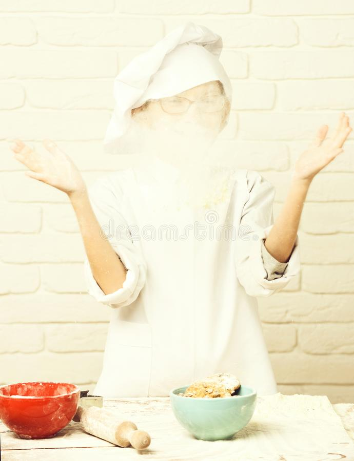 Young boy cute cook chef in white uniform and hat on stained face flour with glasses standing and playing near table. With rolling pin and colorful bowls with royalty free stock photography