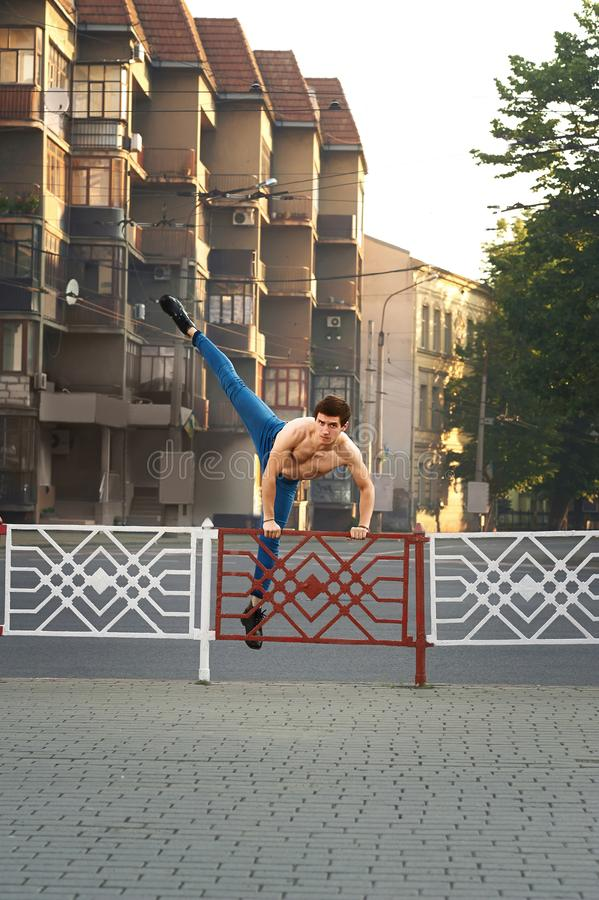 Young boy is dancing on morning`s city streets. stock photo