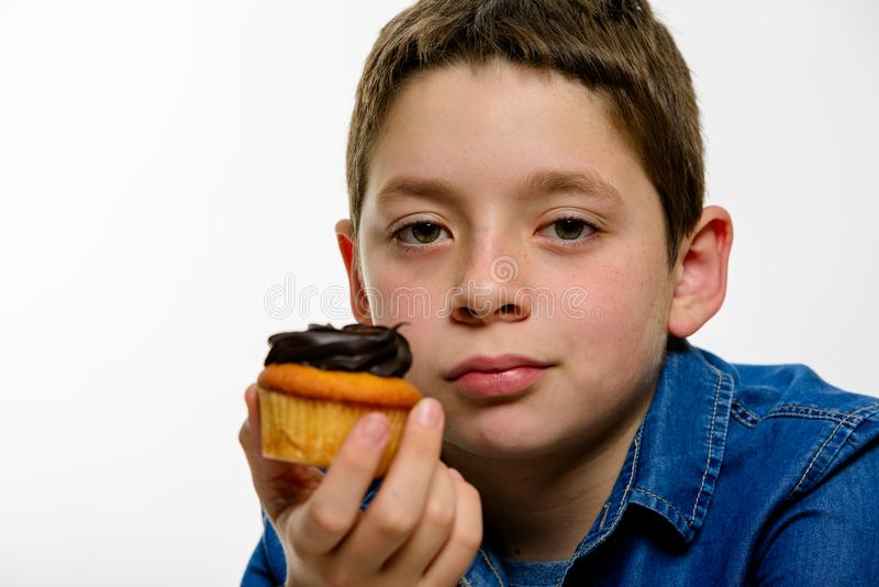 Young boy with denim shirt holding chocolate cupcake, on white isolated background. Close up. stock images