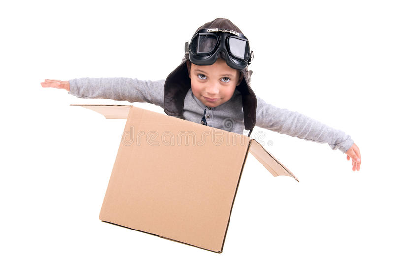 Young boy dream. Young boy pilot playing in a cardboard box isolated in white royalty free stock images