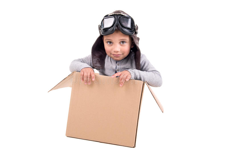 Young boy dream. Young boy pilot playing in a cardboard box isolated in white stock photos