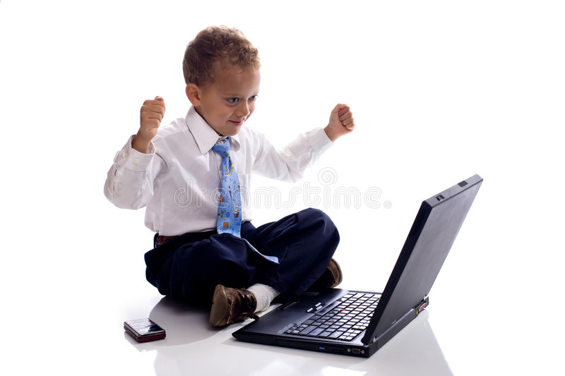 Young boy dressed as businessman works on laptop stock photos
