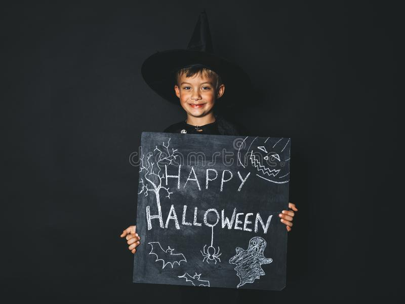 Young boy dressed as a magician is holding happy halloween chalkboard. In front of black background stock photos