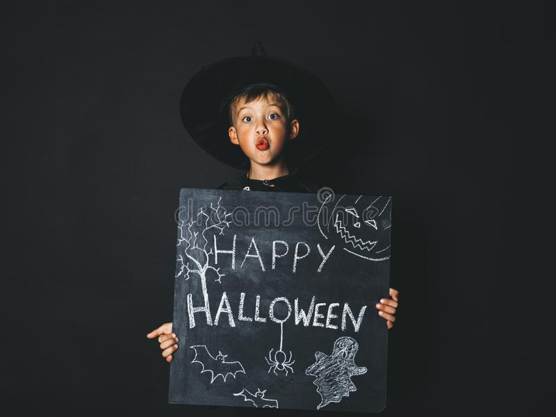 Young boy dressed as a magician is holding happy halloween chalkboard. In front of black background stock photography