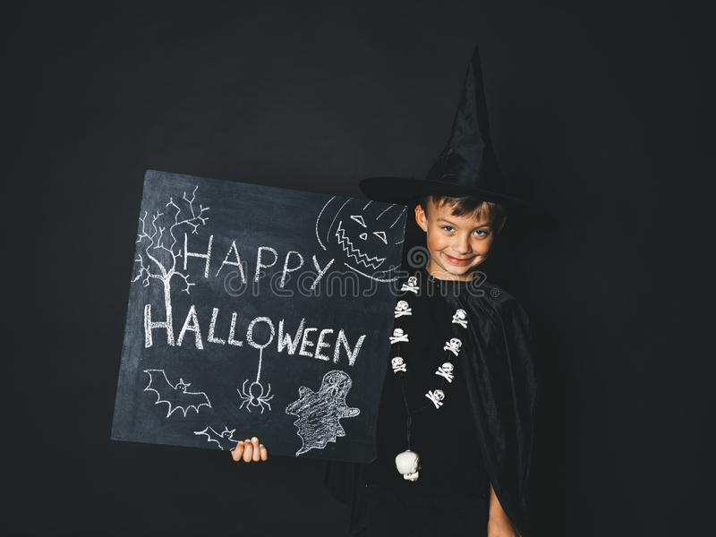 Young boy dressed as a magician is holding happy halloween chalkboard. In front of black background stock images
