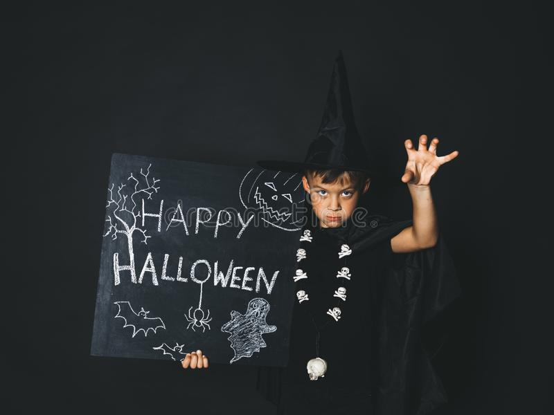 Young boy dressed as a magician is holding happy halloween chalkboard. In front of black background stock image