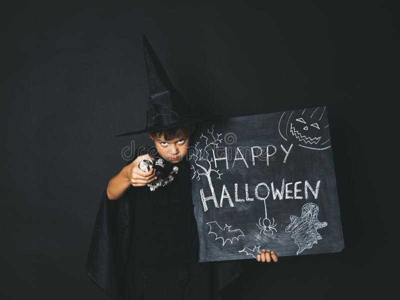 Young boy dressed as a magician is holding happy halloween chalkboard. In front of black background royalty free stock photo
