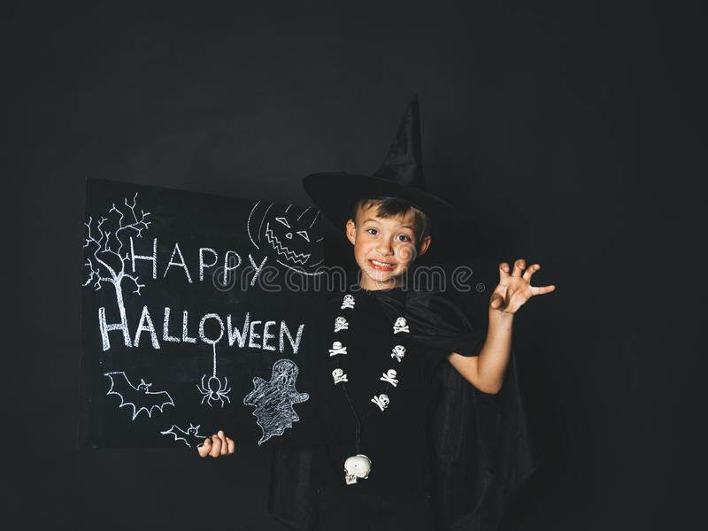 Young boy dressed as a magician is holding happy halloween chalkboard. In front of black background royalty free stock image
